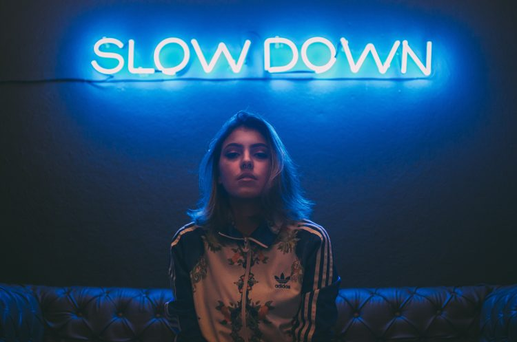 "A beautiful gril in front of a neon sign that says ""Slow Down""."