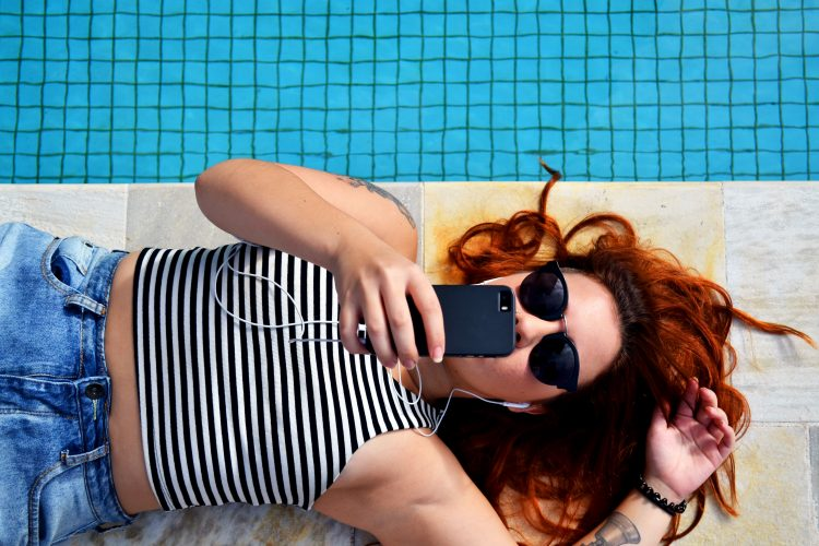A woman by the pool using her mobile phone.