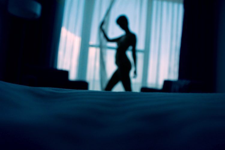 A silhouette of a naked woman standing by the curtain.