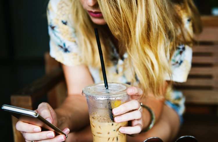 A woman using her mobile device while drinking cold coffee.