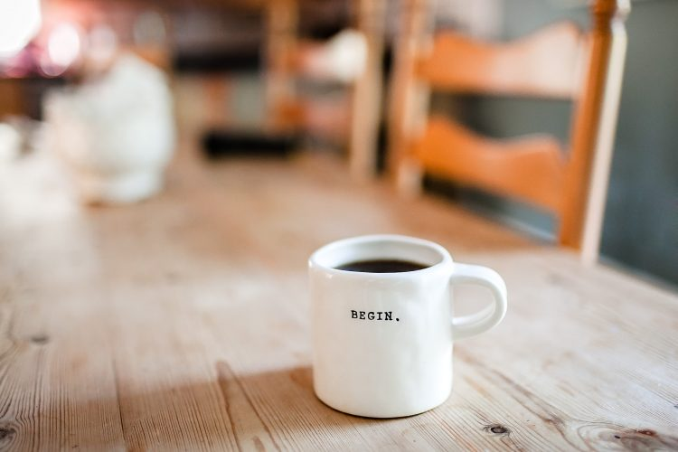 """Coffee in a mug with a """"BEGIN."""" statement."""