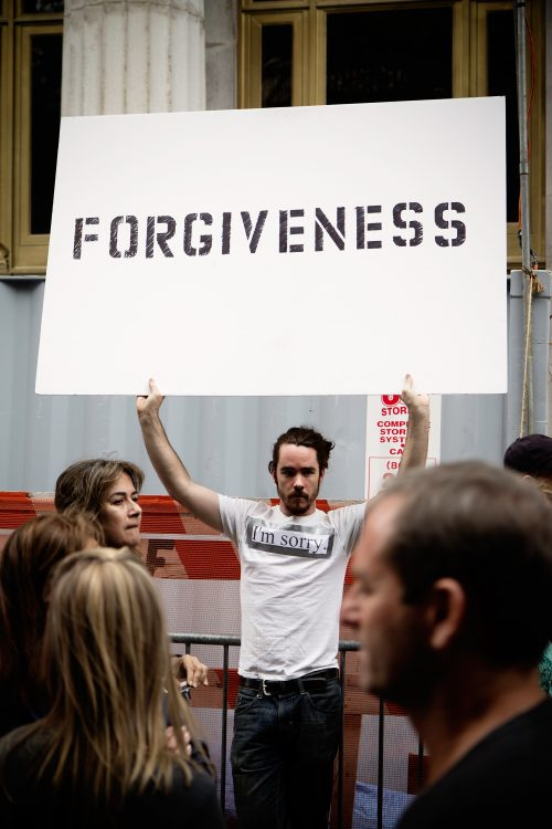 """A man holding a placard that has the word """"FOREGIVENESS"""" written on it."""