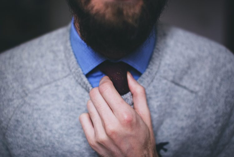 A smartly dressed man fixing his necktie.