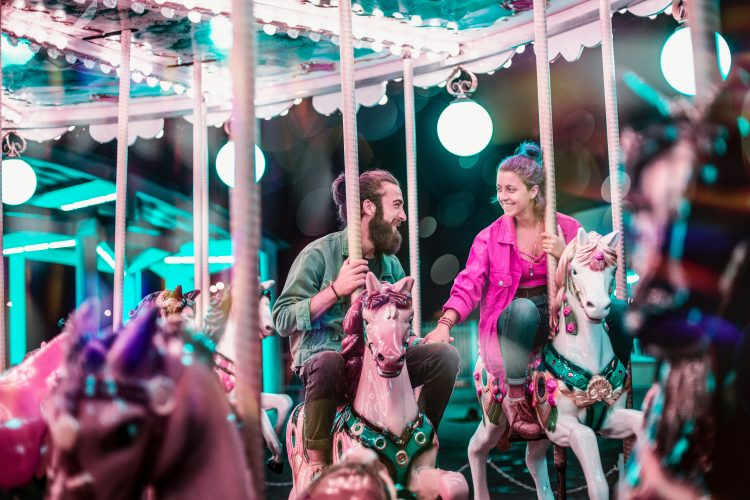 A man and a woman on a date on a carousel.